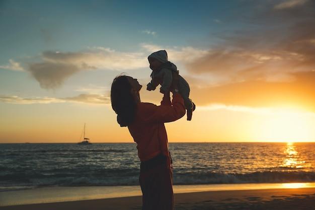 Silhuetas de mãe e bebê ao pôr do sol na praia do oceano no verão. fundo de família feliz