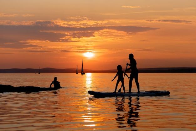 Silhuetas de mãe e filha em stand up paddle board ou sup ao pôr do sol