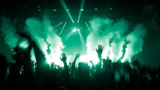 Silhuetas de mãos levantadas em um concerto de música ou festival