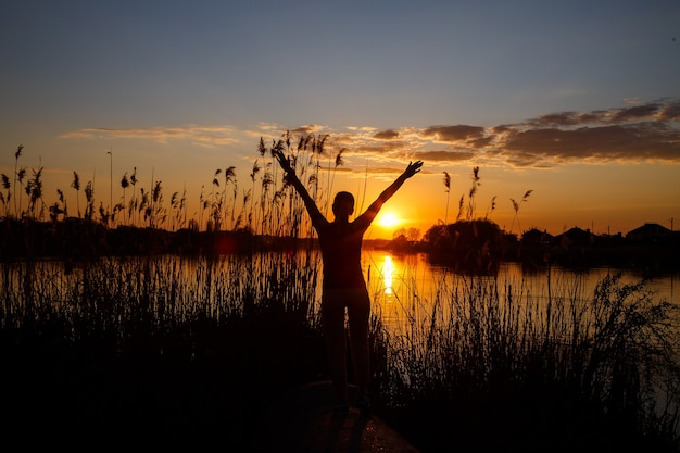 Silhuetas de meninas ao pôr do sol no lago, o sol se põe atrás das árvores e belos reflexos na água