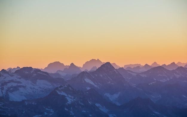 Silhuetas de montanhas ao pôr do sol