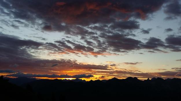 Silhuetas de montanhas rochosas sob um céu nublado durante o pôr do sol ao anoitecer