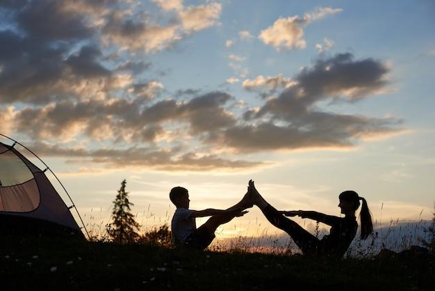 Silhuetas de mulher e menino sentado na grama com flores silvestres e fazendo alongamento ao nascer do sol perto do acampamento. rostos felizes de mãe e filho enquanto pratica esportes sob o céu da manhã