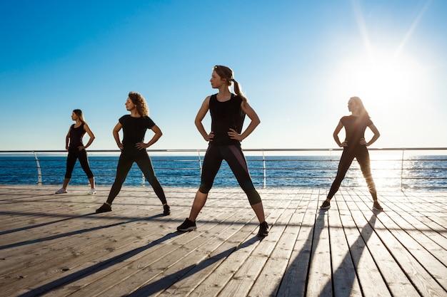 Silhuetas de mulheres esportivas dançando zumba perto do mar ao nascer do sol