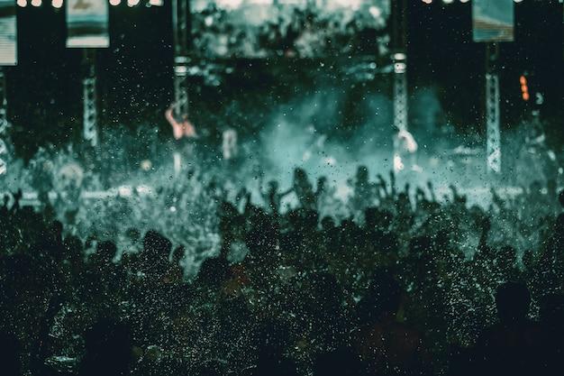 Silhuetas de multidão de concerto na frente de luzes do palco brilhante, festa na piscina