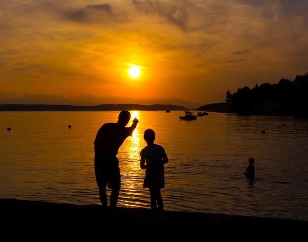 Silhuetas de pai e filha na praia ao pôr do sol