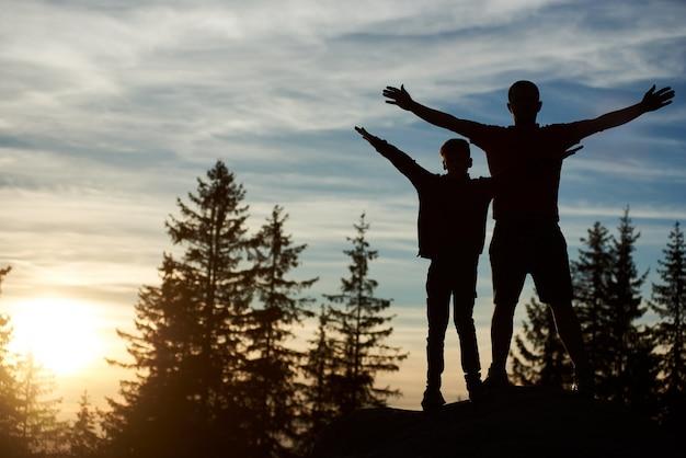 Silhuetas de pai e filho felizes em pé no topo da montanha à noite