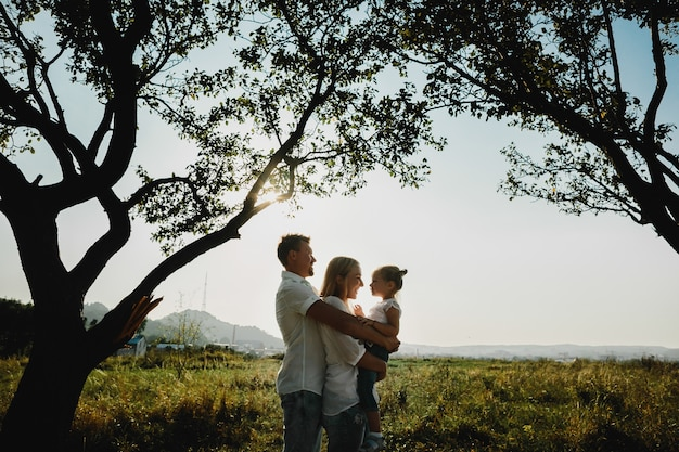 Silhuetas de pais adoráveis brincando com sua filha sob velhas árvores