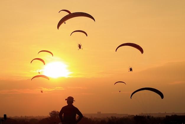 Silhuetas de paramotor ou paratrike ao pôr do sol