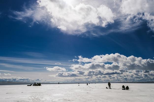 Silhuetas de pescadores de pesca e moto de neve no inverno no gelo