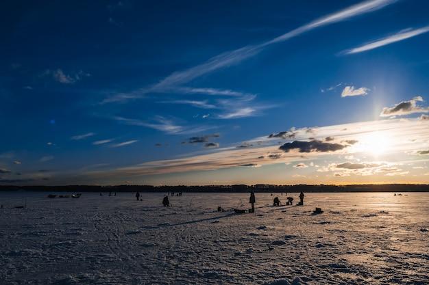 Silhuetas de pescadores que pescam e parafusos de gelo no inverno