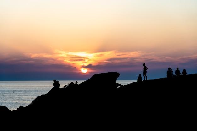 Silhuetas de pessoas ao pôr do sol.