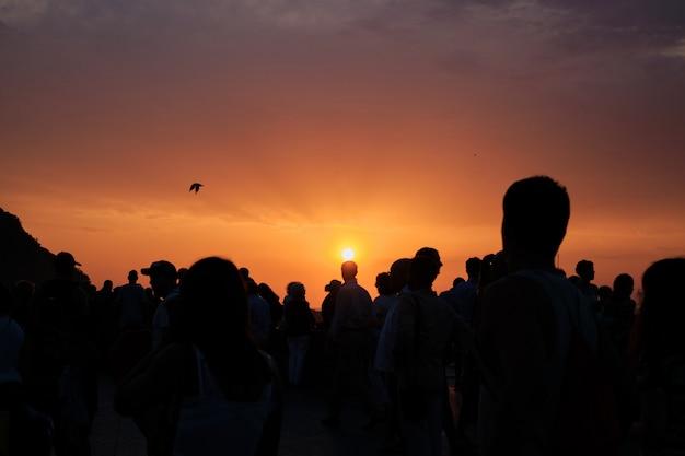 Silhuetas de pessoas ao pôr do sol