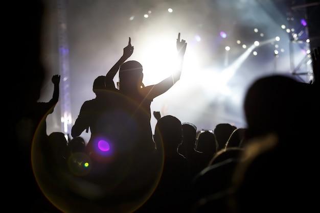 Silhuetas de pessoas com as mãos levantadas no show de música ao ar livre.