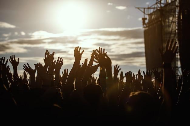 Silhuetas de pessoas com mãos humanas levantadas