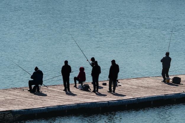 Silhuetas de pessoas com varas de pescar na praia.