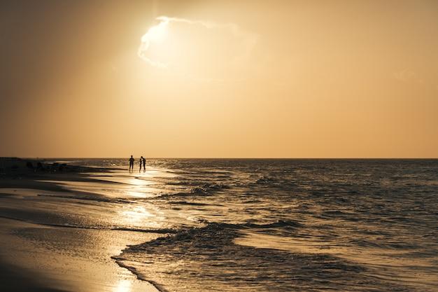 Silhuetas de pessoas contra o pôr do sol no mar. pôr do sol no mar