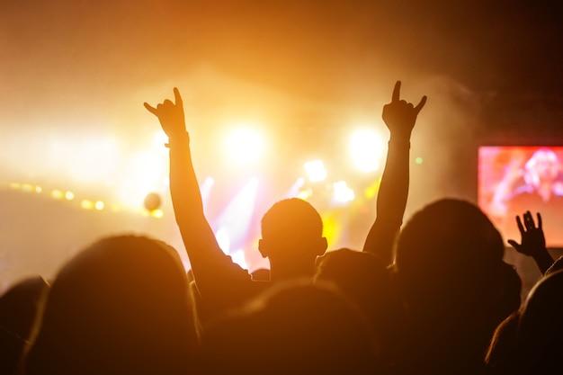 Silhuetas de pessoas em um show em frente à cena sob luz forte