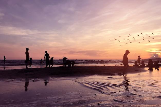 Silhuetas de pessoas na praia tropical no entardecer.
