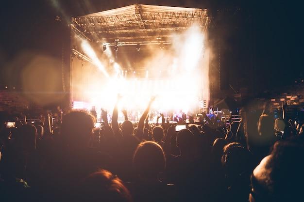 Silhuetas de pessoas no concerto de música. multidão e fãs mostrando amor pela banda de rock no festival
