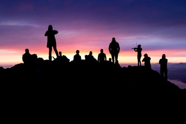 Silhuetas de pessoas no topo de uma montanha