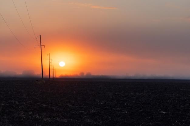Silhuetas de postes transportando eletricidade de alta tensão ao longo de uma estrada em uma área rural. pôr do sol, imagem do nascer do sol com céu nublado de vermelho alaranjado e profundidade de campo sem ninguém no quadro.