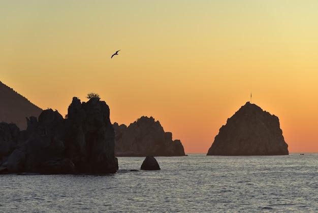 Silhuetas de rochas no mar negro na aldeia de gurzuf a cor dourada do céu ao amanhecer