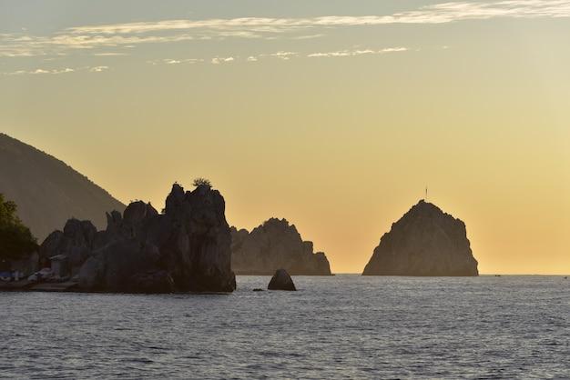 Silhuetas de rochas no mar negro na vila de gurzuf amarelo dourado cor do céu