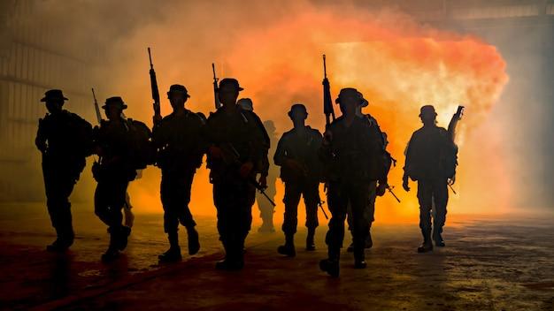 Silhuetas de soldados durante a missão militar ao anoitecer