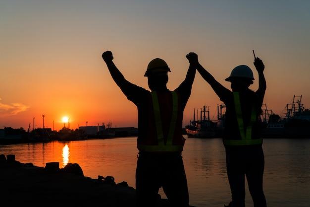 Silhuetas de trabalhador e engenheiro, levantando a mão e em pé no estaleiro. o fundo é o silo de armazenamento de óleo. cooperação no trabalho em equipe e sucesso no trabalho em conjunto conceito.