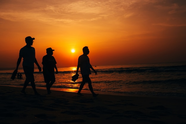 Silhuetas de três homens caminhando na praia ao pôr do sol