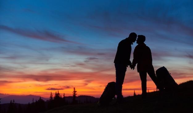 Silhuetas de um casal apaixonado de caminhantes se beijando no topo da montanha, de mãos dadas