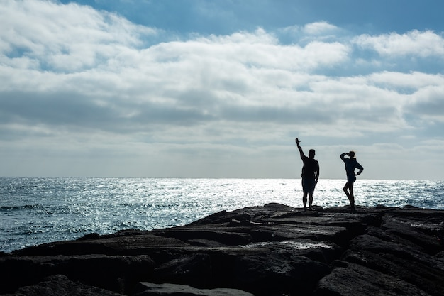 Silhuetas de um homem e uma mulher em um píer de pedra contra o oceano. ilha de lanzarote, espanha.