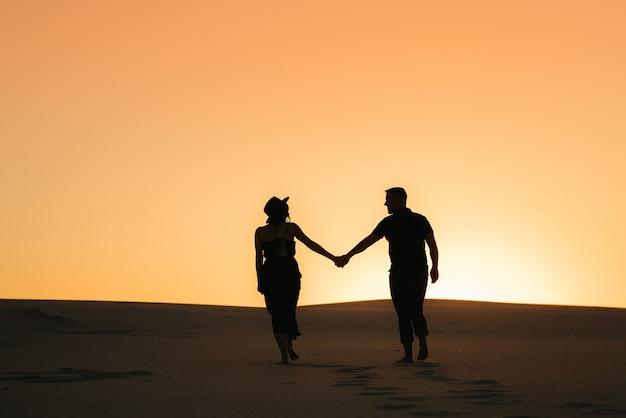 Silhuetas de um jovem casal feliz, cara e mulher