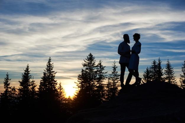 Silhuetas de um jovem casal sentado no topo de uma montanha à noite