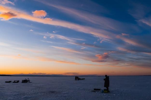 Silhuetas de um pescador com uma vara de pescar em uma pesca de inverno