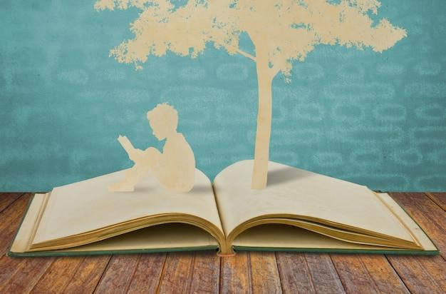 Silhuetas de uma árvore e um homem em um livro