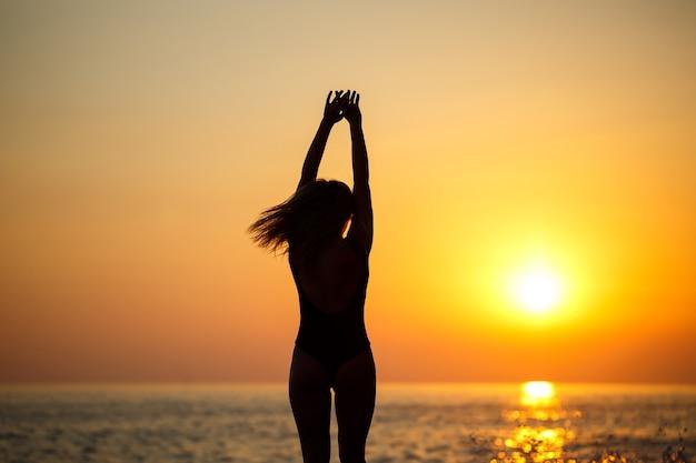 Silhuetas de uma garota contra o fundo do mar e do sol poente