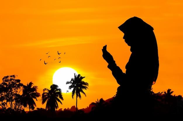 Silhuetas de uma mulher rezando durante o pôr do sol