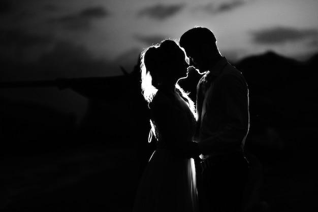 Silhuetas do jovem casal da noiva e do noivo em contraluz