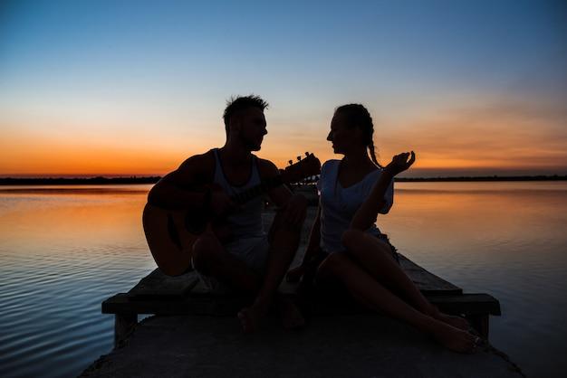 Silhuetas do jovem casal lindo descansando regozijando-se ao nascer do sol perto do lago