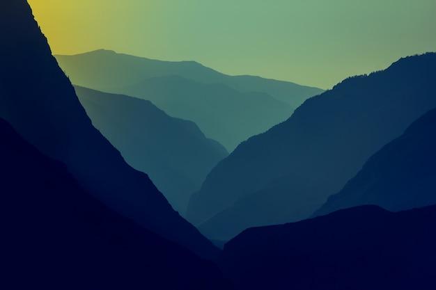 Silhuetas e contornos de um maciço montanhoso no sol poente