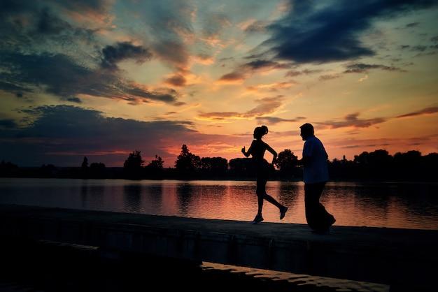 Silhuetas escuras da menina running e do homem sênior quando pôr do sol perto do lago.