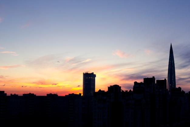 Silhuetas escuras de edifícios urbanos, casas e arranha-céus em plano de fundo por do sol colorido com nuvens cirros