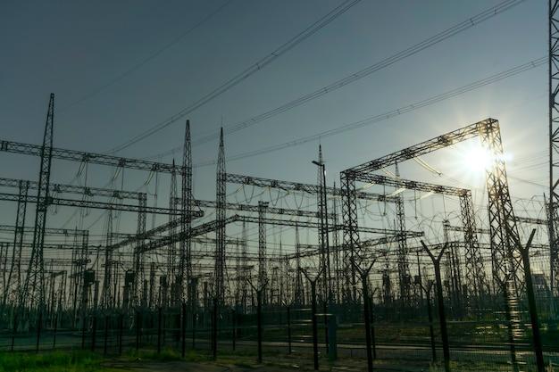 Silhuetas gráficas de diferentes estruturas de uma subestação elétrica em uma luz de fundo