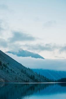 Silhuetas surpreendentes de montanhas e nuvens baixas refletidas no lago de montanha.