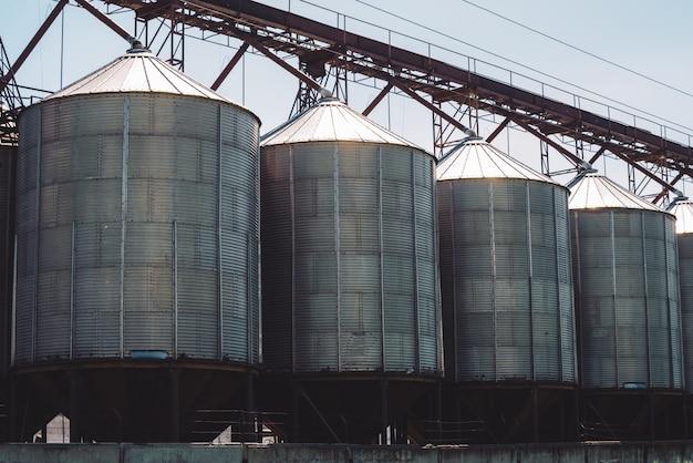 Silos agrícolas. armazenamento e secagem de grãos, trigo, milho, soja, girassol. exterior do edifício industrial. close-up de recipientes de prata metálico grande.