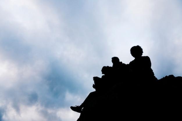 Silueta, de, amigos, sentando, ligado, rocha, contra, céu azul