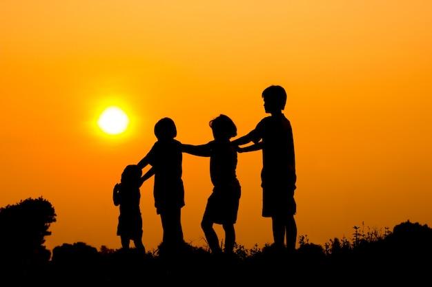 Silueta, de, crianças, tocando, junto, com, pôr do sol