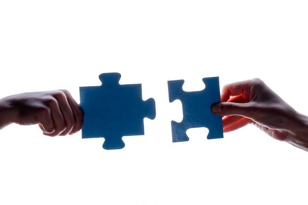 Silueta, de, dois, mão segura, par, de, azul, jigsaw, confunda pedaço, branco